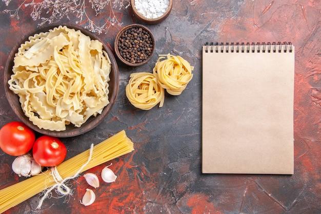 Vista dall'alto di pasta cruda a fette sulla superficie scura pasta pasta cibo scuro