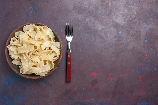 暗い背景の茶色のプレート内のスライスされた生の生地の上面図食事食品夕食パスタ生地 無料写真