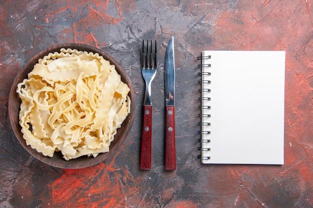 Vista dall'alto a fette di pasta cruda all'interno del piatto sulla superficie scura pasta grezza scura pasta alimentare