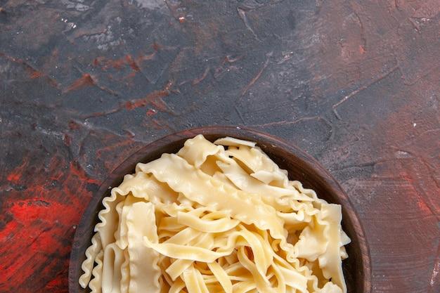 Vista dall'alto a fette di pasta cruda all'interno del piatto sul cibo scuro pasta pasta superficie scura