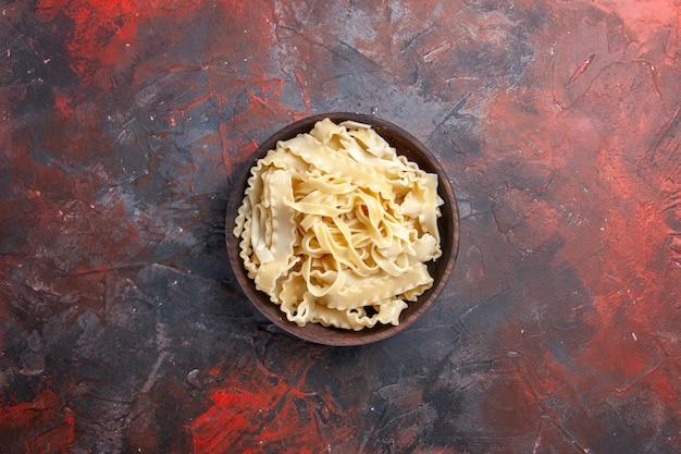 Vista dall'alto a fette di pasta cruda all'interno del piatto su una superficie scura pasta pasta cruda cibo scuro