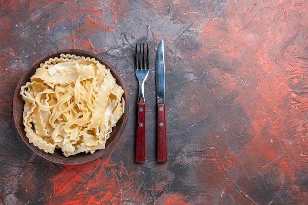 상위 뷰는 어두운 표면에 접시 안에 원시 반죽을 슬라이스 원시 반죽 파스타 어두운 음식
