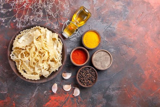 Vista dall'alto di pasta cruda a fette con condimenti su cibo di pasta pasta scura scrivania scura