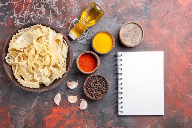 Vista dall'alto di pasta cruda a fette con condimenti su cibo pasta pasta scura pavimento scuro