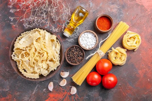 Vista dall'alto a fette di pasta cruda con condimenti su pasta di superficie scura cibo pasta scura