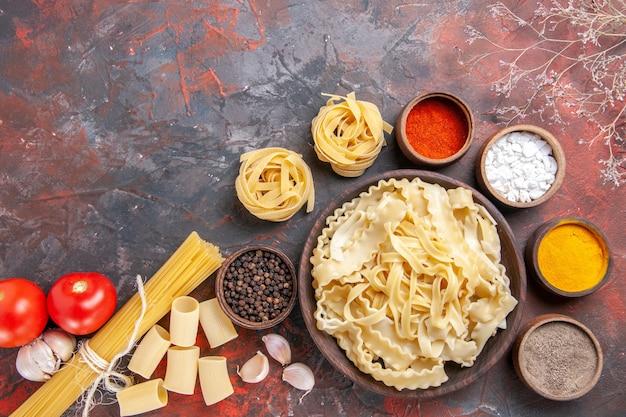Vista dall'alto di pasta cruda a fette con condimenti su cibo scuro pasta pasta superficie scura