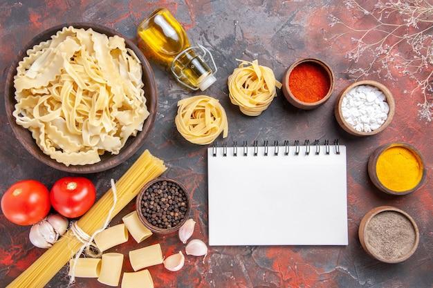 Vista dall'alto di pasta cruda a fette con condimenti su pasta di pasta superficie scura