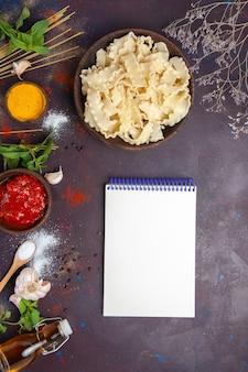 暗い背景の食事ディナーパスタ生地にトマトソースとスライスした生生地の上面図