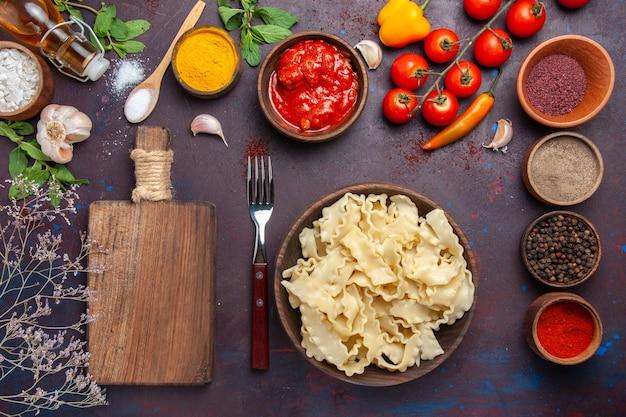 Вид сверху нарезанное сырое тесто с помидорами и разными приправами на темном фоне, тесто, паста, еда, овощи