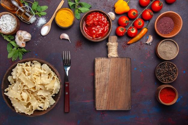 Vista dall'alto a fette di pasta cruda con pomodori e condimenti su sfondo scuro pasta pasta pasto cibo vegetale