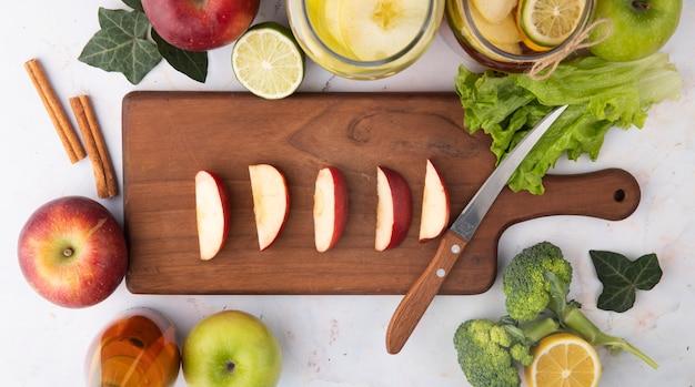 Вид сверху нарезанное красное яблоко на доске с лимонным чаем свежевыжатый яблочный сок брокколи с корицей, ломтик лайма и листья салата