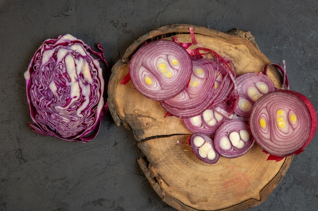 Top view of sliced red cabbage and red onion on a wooden cutting board on black