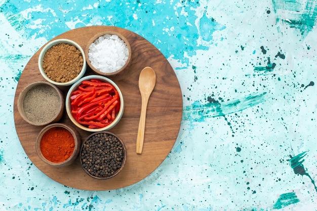 Vista dall'alto peperone rosso a fette con sale pepe e altri condimenti sul colore dell'ingrediente di sale da scrivania azzurro