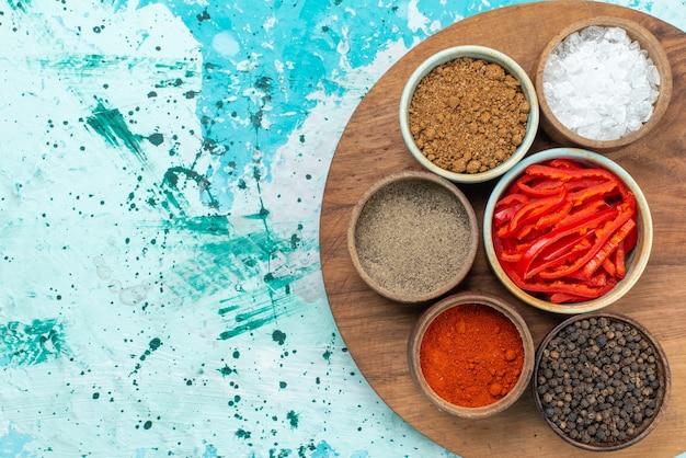 上面図スライスした赤唐辛子と調味料青い背景の塩胡椒のカラー写真