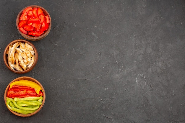 Vista dall'alto di pomodori rossi a fette con pollo e peperoni su nero