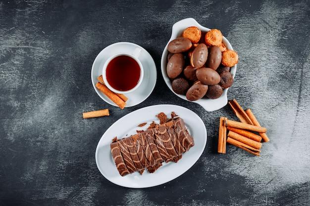 Вид сверху нарезанный рулет в тарелках с чаем, небольшими пирожными и палочками на темной фактуре