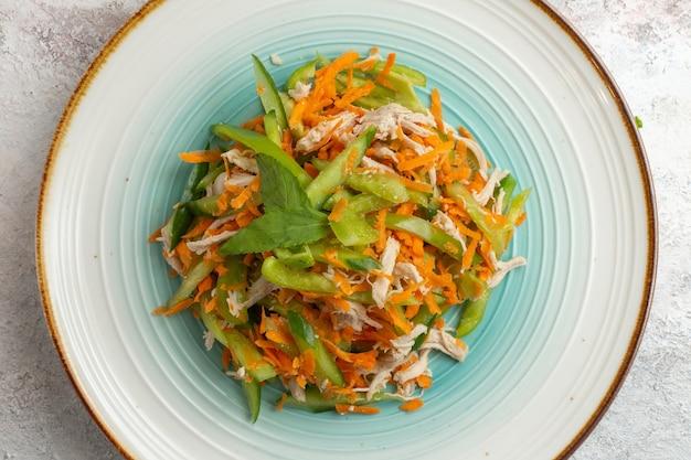 Вид сверху нарезанный салат с курицей внутри тарелки на белом фоне