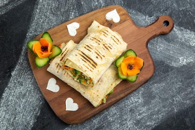 ダークグレーの背景にグリルした肉とスライスしたサンドイッチの上面図ハンバーガーサンドイッチ食品食事パン