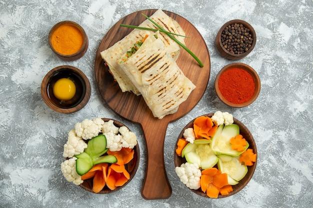 上面図白い背景の上の野菜と調味料のスライスサンドイッチパンミールサンドイッチハンバーガー食品