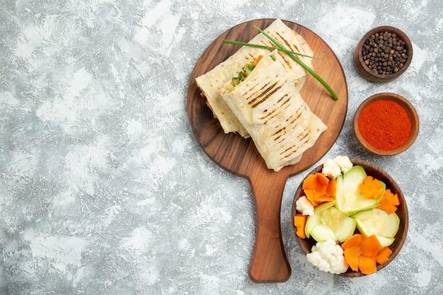 白い背景の上の野菜と調味料とスライスしたサンドイッチの上面図パンサンドイッチハンバーガー食品食事パン