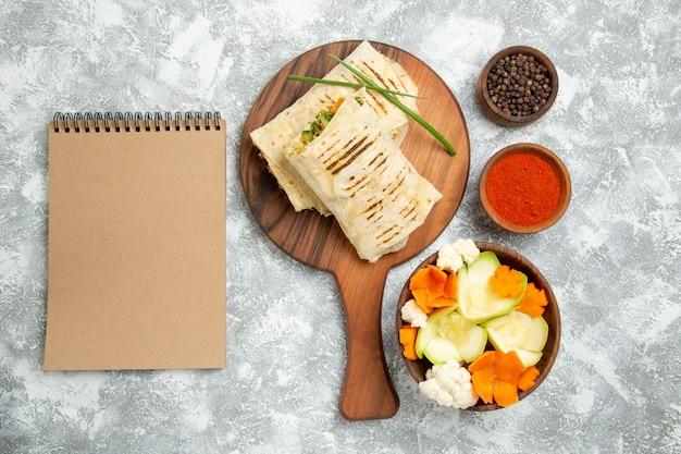 흰색 책상 빵 샌드위치 햄버거 음식 식사 롤빵에 야채와 조미료와 상위 뷰 슬라이스 샌드위치