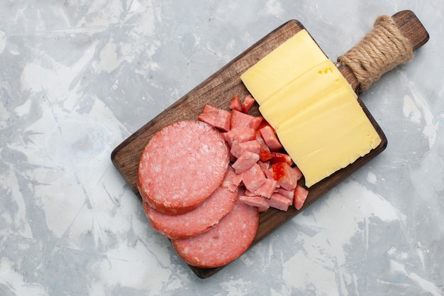 Top view sliced sausages with cheese on white