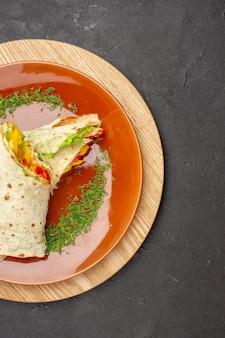 Vista dall'alto del delizioso panino di carne shaurma affettato all'interno del piatto marrone su nero