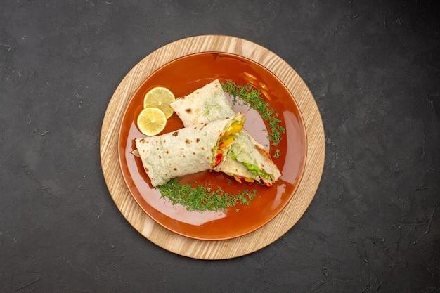 Vista dall'alto del delizioso panino di carne shaurma affettato all'interno del piatto sul nero