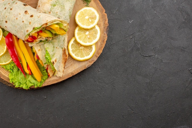 Top view of sliced shaurma delicious meat sandwich with lemon slices on black table