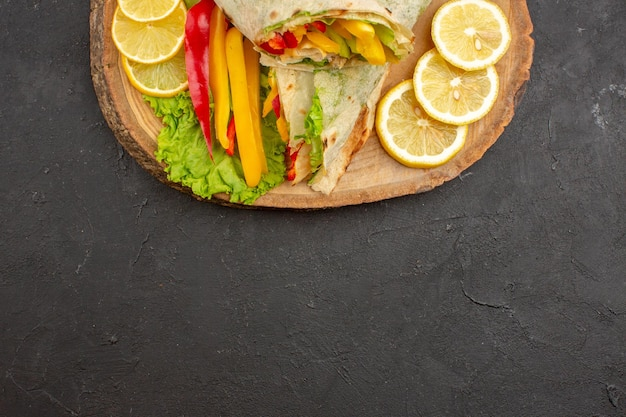 Top view of sliced shaurma delicious meat sandwich with lemon slices on black