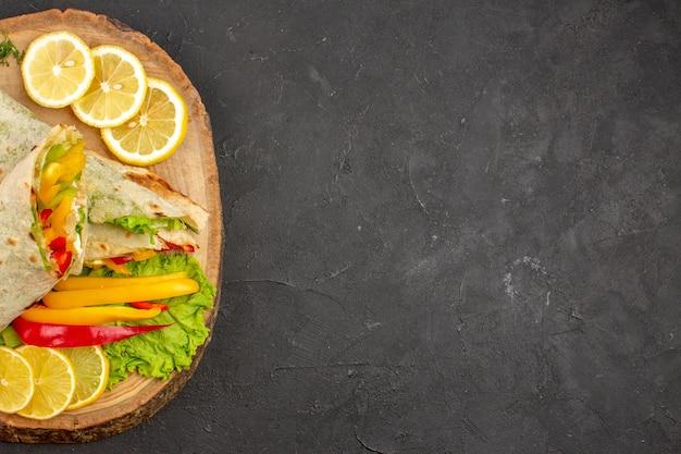 Vista dall'alto del delizioso sandwich di carne shaurma affettato con fette di limone su nero