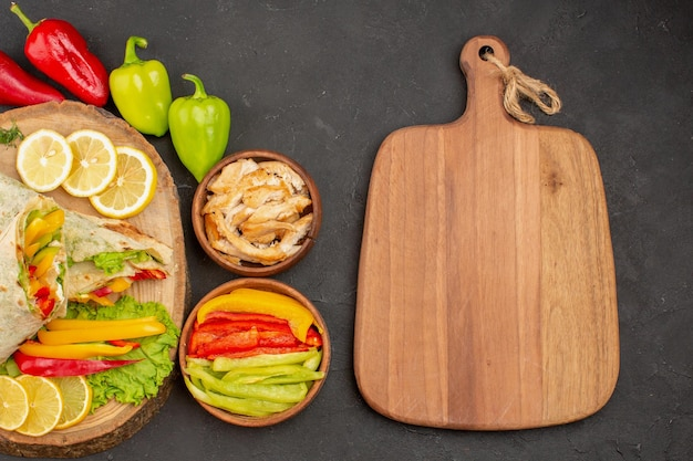 Top view of sliced shaurma meat sandwich with lemon slices and vegetables on black