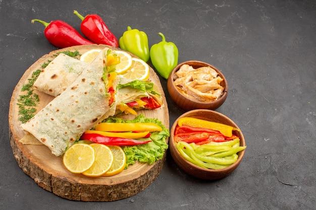 Vista dall'alto del sandwich di carne shaurma affettato con fette di limone e verdure su nero
