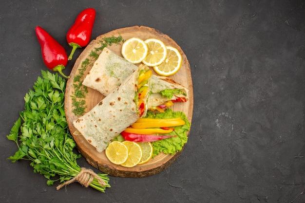 Vista dall'alto del sandwich di carne shaurma affettato con verdure lemonnd su nero
