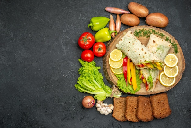 Top view of sliced shaurma sandwich with lemonnd fresh vegetables on black