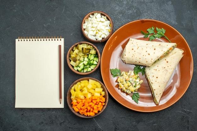上面図スライスしたシャワルマのおいしい肉と灰色の机の上のサラダサンドイッチハンバーガーサンドイッチサラダパンピタ肉