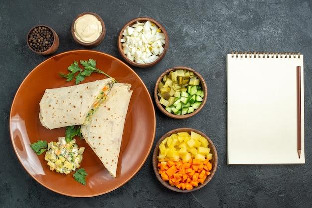 上面図スライスしたシャワルマのおいしい肉と灰色の表面のハンバーガーパンのサラダサンドイッチピタサラダサンドイッチ