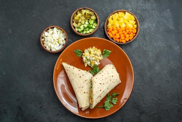 上面図スライスしたシャワルマのおいしい肉と灰色の表面のハンバーガーピタサラダサンドイッチパンのサラダサンドイッチ