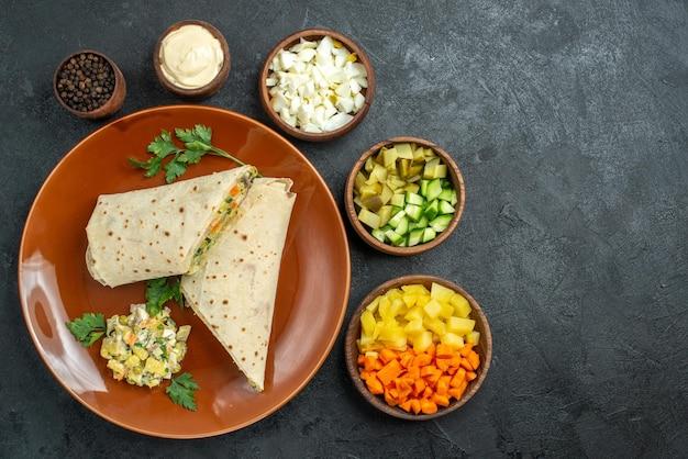 上面図スライスしたシャワルマのおいしい肉と灰色の表面のサラダサンドイッチハンバーガーサンドイッチパンピタミートサラダ