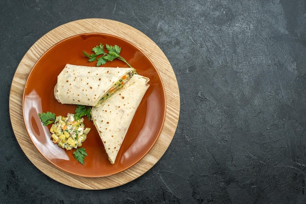 上面図スライスしたシャワルマのおいしい肉と灰色の表面のサラダサンドイッチハンバーガーサンドイッチサラダパンピタ肉