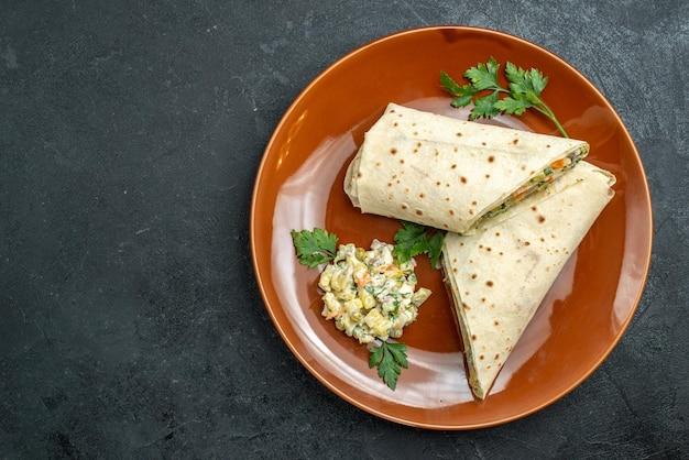 Vista dall'alto shaurma affettato gustoso panino di carne all'interno del piatto sulla superficie scura panino con hamburger e pane pita carne