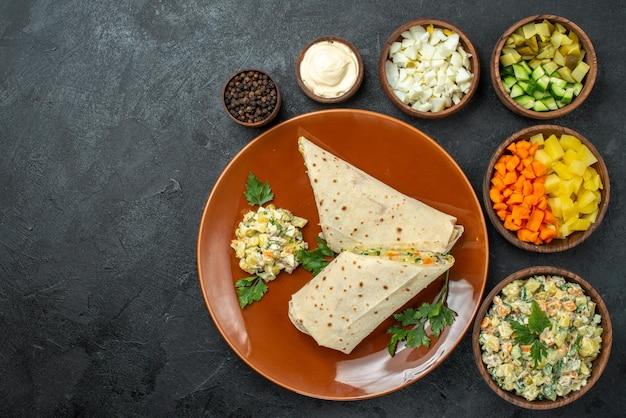 上面図スライスしたシャワルマのおいしい肉サンドイッチ、サラダの材料、暗い表面のハンバーガーサンドイッチパンピタ肉
