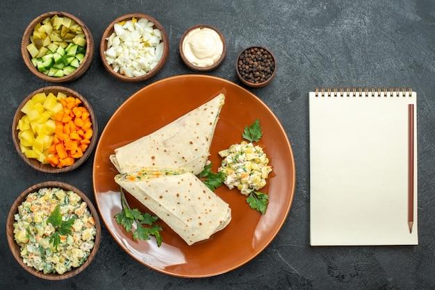 上面図スライスしたシャワルマのおいしい肉サンドイッチ、ダークグレーの表面にサラダの材料を添えたハンバーガーサンドイッチパンのピタ肉