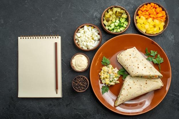 上面図スライスしたシャワルマのおいしい肉サンドイッチ、灰色の表面にサラダの材料を添えたハンバーガーサンドイッチパンピタ肉