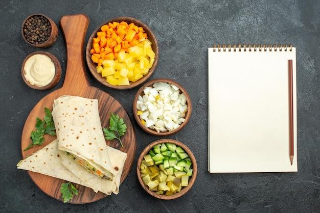 上面図スライスしたシャワルマのおいしいサラダサンドイッチ、灰色の表面に野菜を添えたハンバーガーピタサンドイッチサラダパン