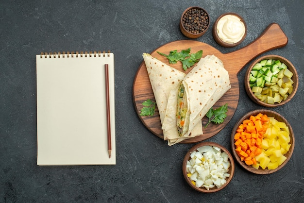 平面図スライスしたシャワルマおいしいサラダサンドイッチと野菜の灰色の机のハンバーガーピタサンドイッチサラダパン