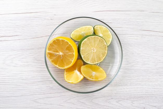 Una vista dall'alto affettato limone aspro succoso all'interno della ciotola di vetro sullo scrittorio bianco, colore succo di frutta