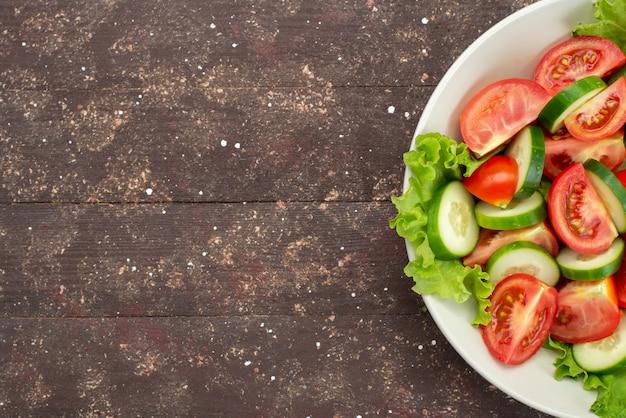 Вид сверху нарезанные помидоры с огурцами внутри белой тарелке с зеленым салатом на коричневом, овощной салат из свежих овощей