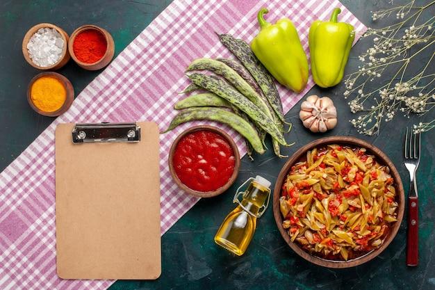 Вид сверху нарезанная овощная еда приготовила вкусное блюдо на синем столе