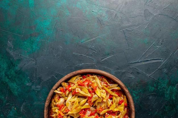 파란색 배경에 다른 재료로 조리 된 상위 뷰 슬라이스 야채 식사